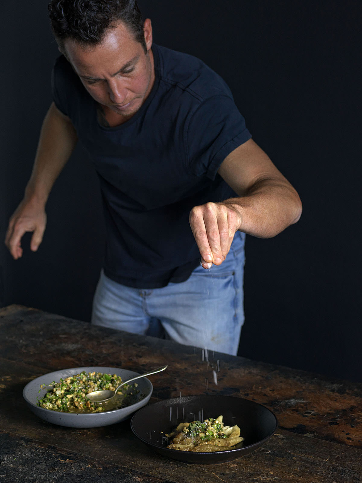 Tom seasoning his smoky eggplant to accompany the flat iron.